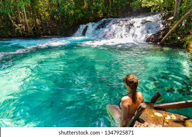 JALAPAO, BRAZIL - CIRCA SEPTEMBER, 2018: Woman looks at the Formiga Waterfall, one of the most popular tourist attractions in the Jalapao region, Tocantins, due to its intensely green/blue waters