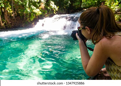 JALAPAO, BRAZIL - CIRCA SEPTEMBER, 2018: Woman photographs the Formiga Waterfall, one of the most popular tourist attractions in the Jalapao region, Tocantins, due to its intensely green/blue waters