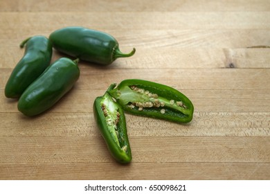 Jalapeno peppers on cutting board with one split open showing seeds