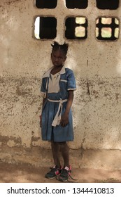 Jali, Gambia, Africa, May 18, 2017: closeup vertical  photography of a young school girl in blue and white uniform standing in front of a vintage wall, outdoors on a sunny day