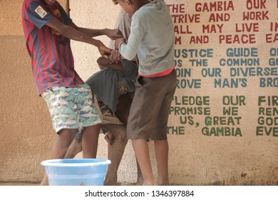 Jali, the Gambia, Africa: may 9, 2018: close up horizontal photography of a group  of teen african  boys fighting in front of school statement sign, outdoors on a sunny da