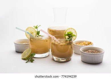 Jal-Jeera OR Jaljira is an Indian beverage prepared using mixing cumin powder in water and served cold with Boondi, Mint and Lemon slice. Served over moody background. Selective focus