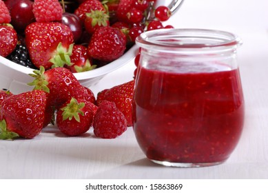 jam in a glass and fresh strawberries