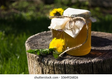 Jam honey of dandelion on a stump tree background in the garden.