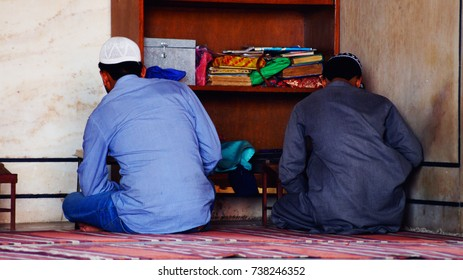 Jama Masjid in details. New Delhi. The prayer hall in the mosque. Muslims during prayer. Parishioners read the Koran.