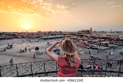 Jamaa el-Fna market Marrakech at sunset. Tourist watching the shops in the old medina.