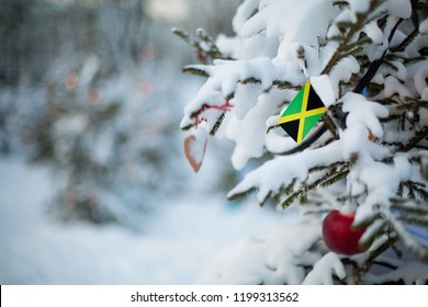 Jamaica flag. Christmas background outdoor. Christmas tree covered with snow and decorations and Jamaican flag. New Year / Christmas holiday greeting card.