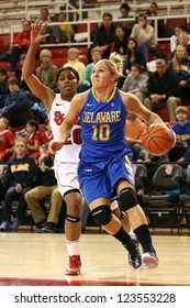 JAMAICA, NY-JAN 2: Delaware Blue Hens guard Kayla Miller (10) drives to the net past St. John's Red Storm guard Keylantra Langley (20) at Carnesecca Arena on January 2, 2013 in Jamaica, New York.