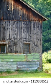 Jamaica, Vermont/USA- August 3, 2014: A horizontal image of a weathered wood plank barn alongside the road of a small rural New England town in summer.