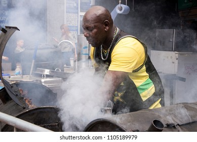Jamaican chef cooking jerk chicken in Food Street Market Reading, United Kingdom - June2, 2018