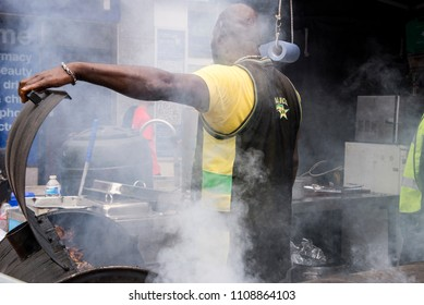 Jamaican chef cooking jerk chicken in Food Street Market Reading, United Kingdom - June 2, 2018