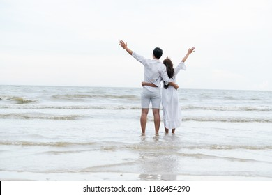 Jamaican couple travel honeymoon in Jamaica. The couple wearing all white costume standing on the beach.