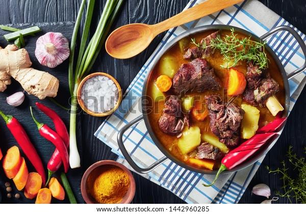 ジャマイカのカレー料理の山羊 – 黒い木のテーブルの上に、切り板の上に具材の入った鍋に、実においしい遅い調理のジャマイカのスパイスカレー、上から見ると平らなレイ、接写