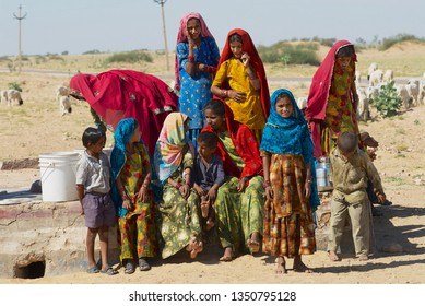 Jamba, India - April 02, 2007: Group of young women and kids wearing traditional dresses collect water from a public road side well  in the Great Thar desert in Jamba, India.