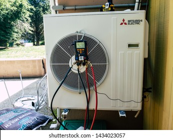 Jamestown, Rhode Island, USA July 20th, 2019 Wall hung Mitsubishi ductless mini split system being inspected for summer air conditioning operation.