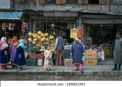 Jammu and Kashmir, India - April 12, 2019 : Kashmiri people waiting for the bus in front of the miscellaneous shops on footpath countryside perimeter of Srinagar, Kashmir, India