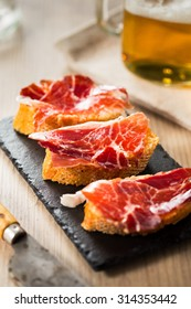 Jamon iberico, the best spanish ham tapas on a slice of bread and beer.