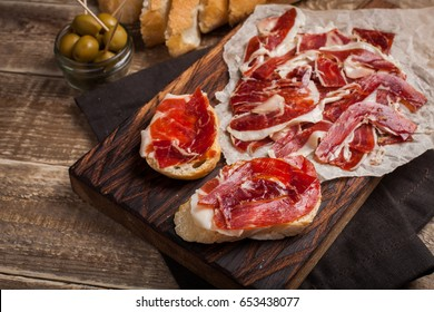Jamon Iberico with white bread, olives on toothpicks and fruit on a wooden background. Top view