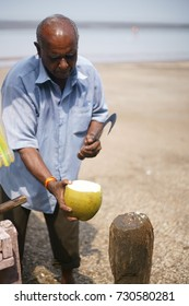 JAMPORE BEACH, DAMAN, INDIA - OCTOBER 9, 2017: A portrait of a old Hard working man cutting and selling coconuts to tourists, at the JAMPORE BEACH, DAMAN, INDIA.