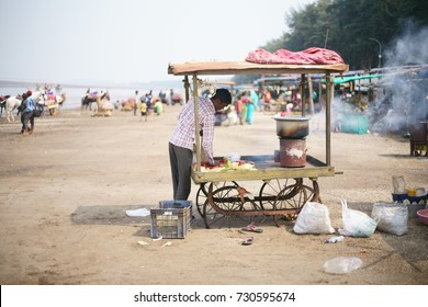JAMPORE BEACH, DAMAN, INDIA - OCTOBER 9, 2017: A portrait of a Hard working Indian man setting up his tea, snacks and fast food stall to sell to visiting tourists, at the JAMPORE BEACH, DAMAN, INDIA.