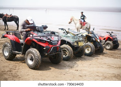 JAMPORE BEACH, DAMAN, INDIA - OCTOBER 9, 2017: A couple of young men are seen providing tourists with ATV (All Terrain Vehicle) rides, at the JAMPORE BEACH, DAMAN, INDIA.