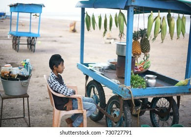 JAMPORE BEACH, DAMAN, INDIA - OCTOBER 9, 2017: A portrait of a young Hard working boy selling Indian fast food & snacks to tourists, at the JAMPORE BEACH, DAMAN, INDIA.