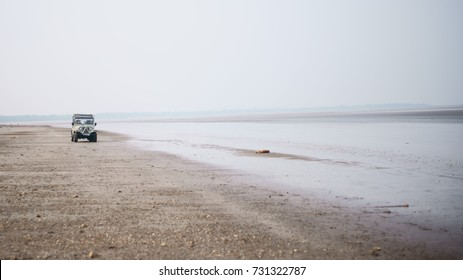 JAMPORE BEACH, DAMAN, INDIA - OCTOBER 8, 2017: A wide angle shot of some Indian tourists riding an open air jeep, at the JAMPORE BEACH, DAMAN, INDIA.