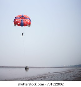 JAMPORE BEACH, DAMAN, INDIA - OCTOBER 9, 2017: A man/tourist is seen flying high in a parachute during a Parasailing session, at the JAMPORE BEACH, DAMAN, INDIA.