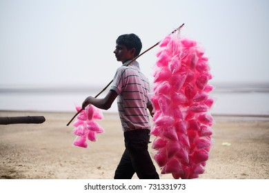 JAMPORE BEACH, DAMAN, INDIA - OCTOBER 9, 2017: A portrait of a young Hard working man selling cotton candy to tourists, at the JAMPORE BEACH, DAMAN, INDIA.