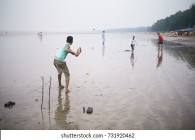JAMPORE BEACH, DAMAN, INDIA - OCTOBER 9, 2017: A group of young guys/ tourists are enjoying a game of beach cricket at the JAMPORE BEACH, DAMAN, INDIA.