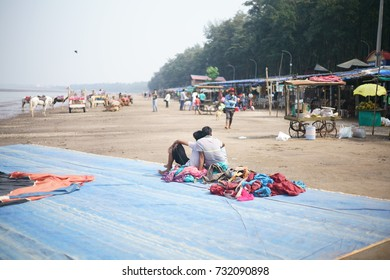 JAMPORE BEACH, DAMAN, INDIA - OCTOBER 9, 2017: A group of men are sitting on the floor and waiting for the Parasailing session to begin, at the JAMPORE BEACH, DAMAN, INDIA.
