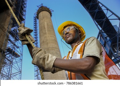 Jamshedpur, Jharkhand India May,17,2011Low angle Close up portrait of worker pulling rope at construction site, with safety gear against tall chimney and blue sky background, Jharkhand, India