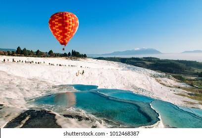 JAN 1, 2018 Pamukkale, Denizli, Turkey : Hot air balloon flying over Travertine pools limestone terraces on a beautiful day