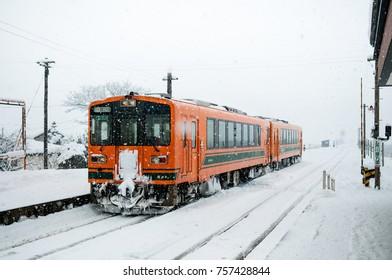 JAN 21, 2014 Aomori, Japan : Orange color Train on snow covered tracks of Tsugaru railway line in mid winter at Goshogawara station, Aomori, Tohoku, Japan.