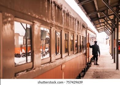 JAN 21, 2014 Aomori, Japan : Train conductor officer waiting passenger to board on classic old potbelly stove train opperated on Tsugaru railway in winter snow at Goshogawara station, Aomori,  Japan.