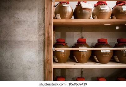 JAN 28, 2013 Naha, Okinawa, JAPAN : Vintage Ceramic clay pottery art, Ceramic vase, jar, jug, Awamori Okinawa liqueur bottle on shelf