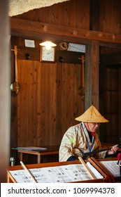 JAN 28, 2013 Naha, Okinawa, JAPAN : Old man in traditional cloth and hat playing Sanshin Okinawa - Japanese traditional vintage music instrument