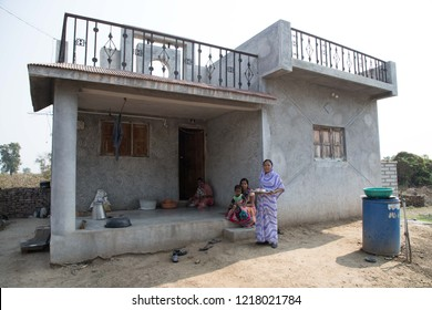 Jan 9, 2018: Vari village, Maharashtra, India: a family and their concrete village house with a water tank. lady holding tea tray in Indian villages near Godavari river