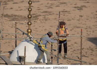 JANABIYA, BAHRAIN - 20 MAY, 2018: Two workmen with safety harnesses erect scaffolding at the top of a minaret of a mosque under construction against a desert backdrop.