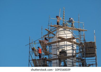 JANABIYA, BAHRAIN - 20 MAY, 2018: Workmen with safety harnesses erect scaffolding at the top of a minaret of a mosque under construction against a blue sky backdrop.