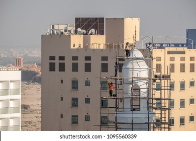 JANABIYA, BAHRAIN - 20 MAY, 2018: Workmen with safety harnesses erect scaffolding at the top of a minaret of a mosque under construction against a backdrop of apartment blocks.