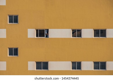 JANABIYA, BAHRAIN - 20 MAY, 2018: A woman takes a photo with a mobile device from the window of her apartment block.