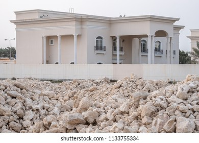 JANABIYA, BAHRAIN - 26 JANUARY, 2018: Piles of stone for construction sit in front of walled private villa with elaborate pillars and balconies.