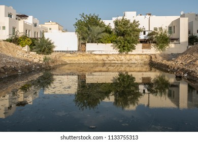 JANABIYA, BAHRAIN - 3 MARCH, 2017: Water reflects the surrounding villas in a plot dug for work to start on foundations of a building in a housing development in Bahrain.
