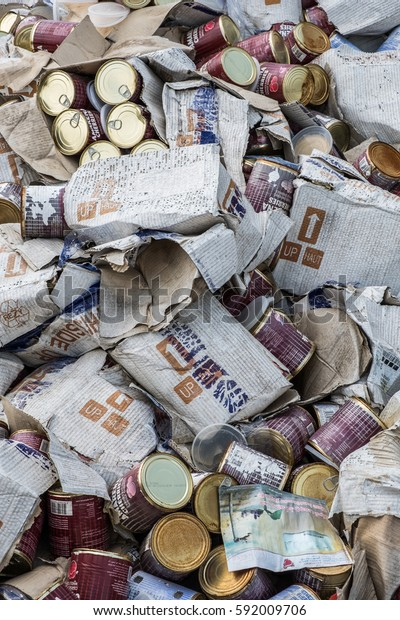 JANABIYA, BAHRAIN - 3 MARCH 2017: Hundreds of tin cans of discarded, expired cherries lie dumped as trash in their cardboard boxes.