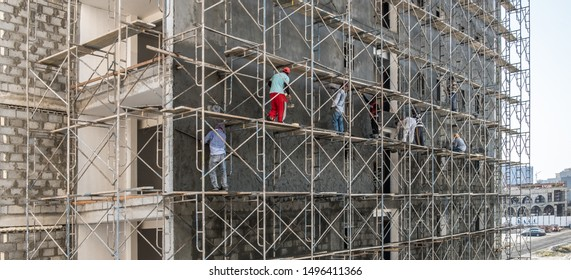 JANABIYA, BAHRAIN - OCTOBER 20, 2017: Asian migrant workers plaster the facade of an apartment building on a scaffolding frame of a housing development in the Middle East.