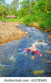 Janda Baik, Malaysia - August 30, 2015 : Motion blur image of a girl swimming and enjoying cold natural water at Janda Baik Resort, Pahang, Malaysia
