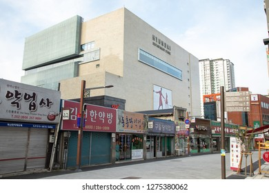 Janggwan-Dong, Daegu, South Korea - October 8 2018: Old Asian street market in downtown Daegu, with a looming Hyundai Department Store in the background