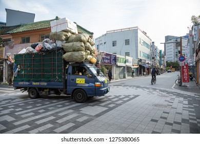 Janggwan-Dong, Daegu, South Korea - October 8 2018: Asian garbage truck crossing an intersection, with downtown Daegu in the background