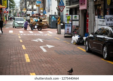 Janggwan-Dong, Daegu, South Korea - October 9 2018: View up a side street in downtown Daegu, with an old lady pushing a recycling cart in the distance
